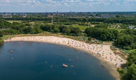 Luchtfoto van mensen die verkoeling zoeken in en op het water.